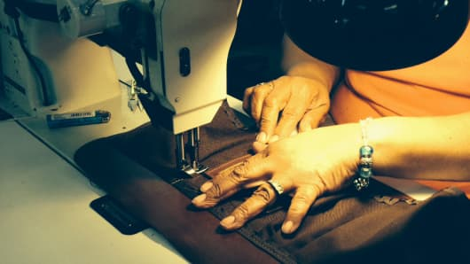 A worker sewing at J.W. Hulme.